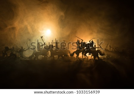 Medieval battle scene with cavalry and infantry. Silhouettes of figures as separate objects, fight between warriors on dark toned foggy background. Night scene. Selective focus Royalty-Free Stock Photo #1033156939