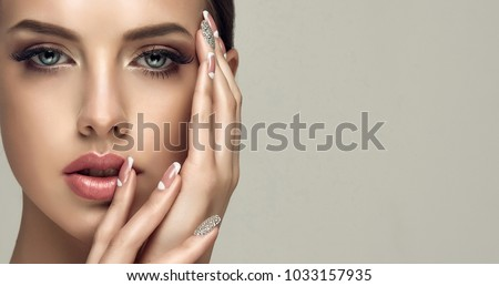 Beautiful model girl with a beige French manicure nail design with rhinestones . Fashion makeup and care for hands and nails and cosmetics . #1033157935