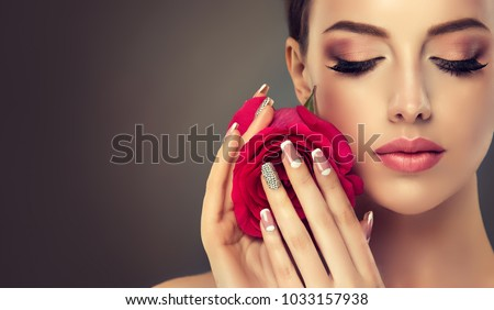 Beautiful model girl with a beige French manicure nail design with rhinestones. Fashion makeup and care for hands and nails and cosmetics. Royalty-Free Stock Photo #1033157938