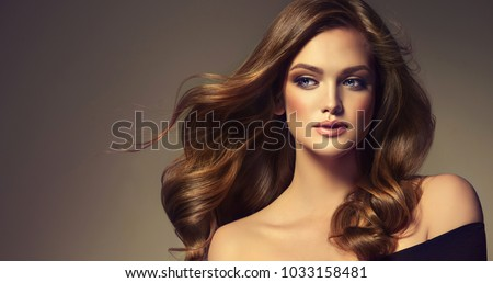 Brunette  girl with long  and   shiny curly hair .  Beautiful  model woman  with wavy hairstyle   .Care and beauty of hair #1033158481