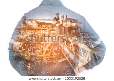 Double exposure of Engineer or Technician man holding safety helmet operated platform or plant for industry 4.0  with offshore oil and gas platform background for industrial business concept. #1033192528