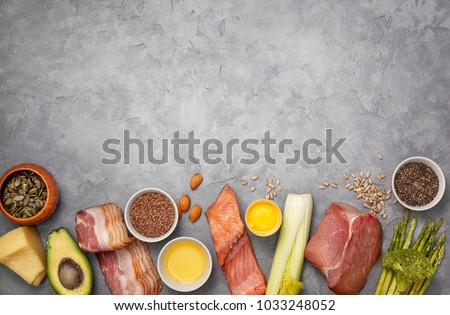Ingredients for ketogenic diet: meat, bacon, fish, broccoli, asparagus, avocado, mushrooms, cheese, sunflower seeds, chia seeds, pumpkin seeds, flax seeds. view from above. copy space #1033248052