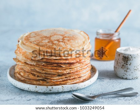 Stack of traditional russian pancakes blini on gray background with copy space. Homemade russian thin pancakes blini. Russian food, russian kitchen #1033249054