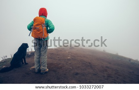 woman backpacker and dog on mountain top in bad weather #1033272007