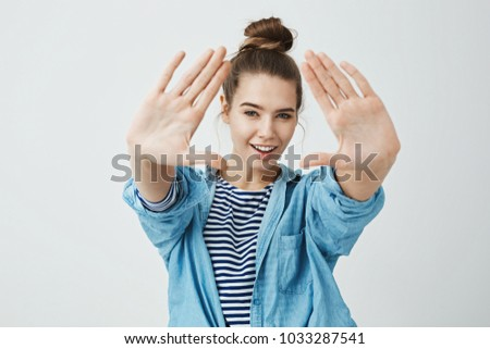 Girl is keeping eye on you. Portrait of emotive joyful caucasian woman pulling hands towards camera, making triangle and looking through it with broad smile and knowing look, standing over gray wall