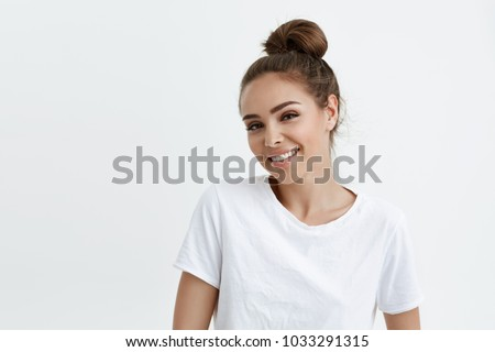 Waist-up portrait of cheerful attractive modern woman with bun, smiling broadly at camera and expressing positive emotions wjile standing over white background. Do you want to hang around sometime