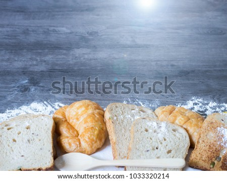 Freshly baked delicious bread and croissant on a wooden worktop with green leave and copy space, healthy eating concept  #1033320214
