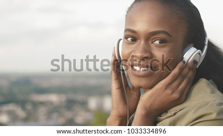 Beautiful attractive african girl with natural make-up and lovely smile is listening to music in her headphones at the blurred background of the city. #1033334896