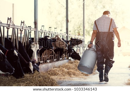 farmer asian are holding a container of milk on his farm.walking out of the farm #1033346143