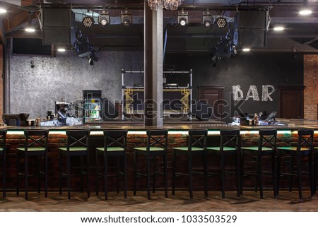 bar counter with bar chairs in loft style design, strobe light on dark ceiling #1033503529