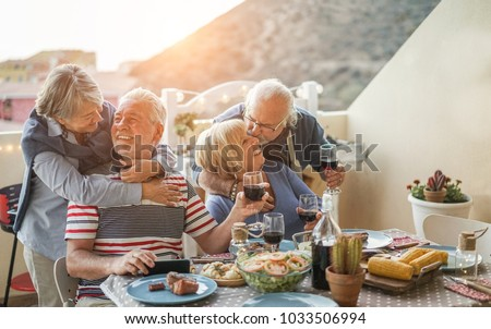 Senior couples having fun at barbecue dinner in home terrace - Pensioner friends having cute tender moments at bbq meal - Focus on right man - Love and jouyful elderly lifestyle concept #1033506994