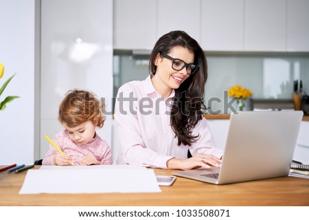 Working mother concept. Young woman working on laptop with her child from home #1033508071