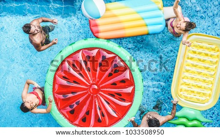 Happy friends playing with air lilo ball inside swimming pool - Young people having fun on summer holidays vacation - Travel, holidays, youth lifestyle, friendship and tropical concept Royalty-Free Stock Photo #1033508950