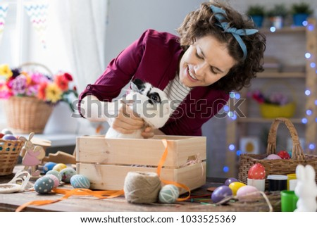 Portrait of young woman smiling happily while playing with cute Easter bunny sitting in wooden box #1033525369