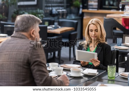 businesswoman using tablet during business meeting with colleague in cafe #1033545055
