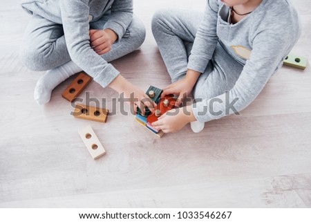 Children play with a toy designer on the floor of the children's room. Two kids playing with colorful blocks. Kindergarten educational games. #1033546267