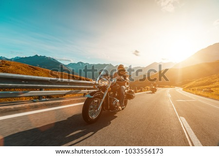 Motorcycle driver riding japanese high power cruiser in Alpine highway on famous Hochalpenstrasse, Austria, central Europe. #1033556173