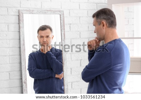 Thoughtful mature man standing near mirror at home Royalty-Free Stock Photo #1033561234