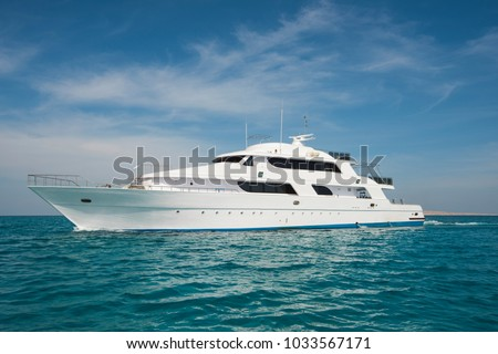 A luxury private motor yacht under way on tropical sea with bow wave Royalty-Free Stock Photo #1033567171