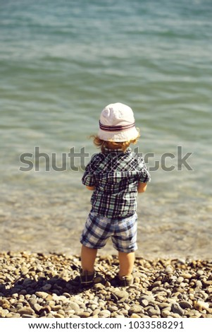 Baby boy cute fair-haired blond kid tiny little child wearing checked shirt shorts and white hat standing on pebble beach on sunny day back view on beautiful seascape background, vertical picture
