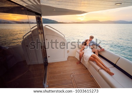 Romantic vacation and luxury travel. Young loving couple sitting on the sofa on the modern yacht deck. Sailing the sea. #1033615273
