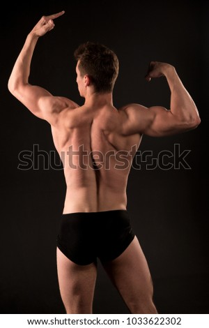 Man athlete with muscular body, torso, back view. Bodybuilder pose on dark background. Sportsman with strong hands, biceps, triceps. Power, health, wellness, bodycare. dieting #1033622302