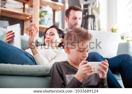 Family with laptop, tablet and smartphone at home, everyone using digital devices Royalty-Free Stock Photo #1033689124