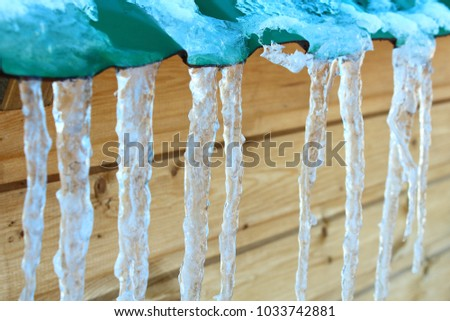 Icicles close-up on the edge of the roof made of corrugated board. Background. #1033742881
