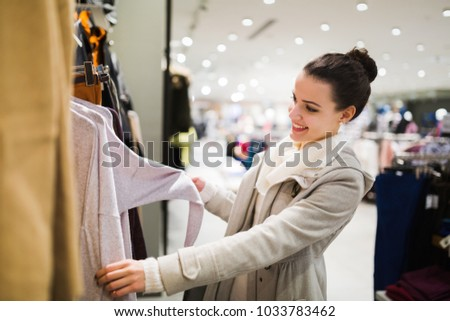 Young attractive woman buying clothes in mall #1033783462