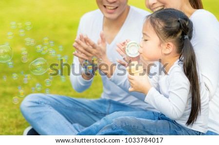 Happy young father  and her daughter blowing soap bubbles together in park.Family happiness and carefree concept. #1033784017