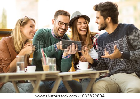 Group of four friends having a coffee together. Two women and two men at cafe talking laughing and enjoying their time using digital tablet. #1033822804