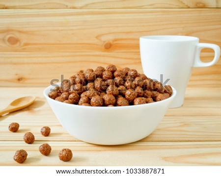 Chocolate cereal balls in a bowl on wooden background. Healthy breakfast concept. #1033887871