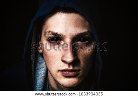 Man with black eyes on dark black background