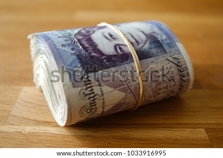 A rolled up bunch of bank notes, giving the impression of wealth. #1033916995