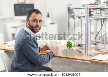 Love this task. Charming upbeat engineer sitting at his work desk with a 3D printer on it and working on the eco-city project while holding a model of a house in his hands #1033928023