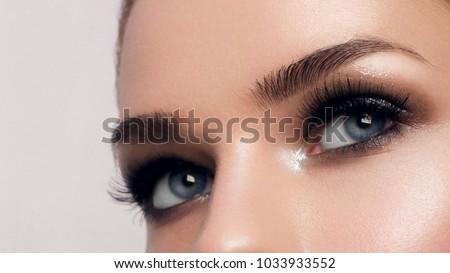 Macro shot of woman's beautiful eye with extremely long eyelashes. Sexy view, sensual look. Female eye with long eyelashes #1033933552