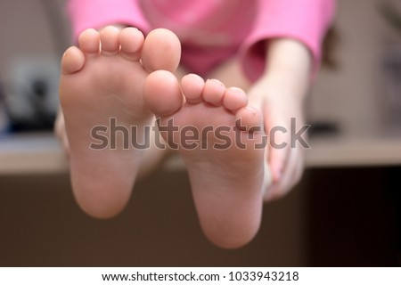 Kids toes and heels. Baby shows foots. #1033943218