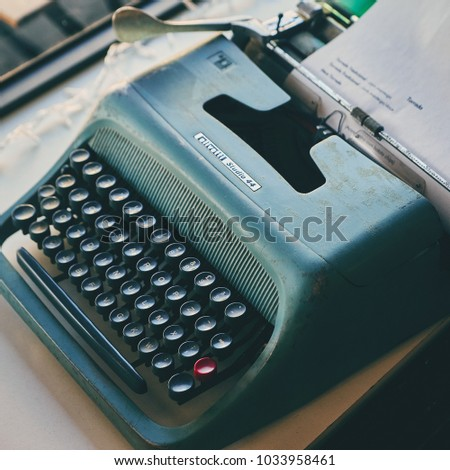 Lisbon, Portugal - February, 2018. Photo of retro objects in the lounge of a cafe in the suburbs of Lisbon. Vintage typewriter of blue-green color with black keys and one red key. #1033958461