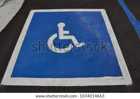 Restricted Disability Parking painted within designated parking space #1034014663