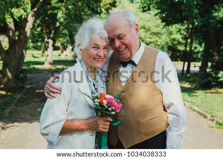 Old couple is walking in the green park. Grandmother and grandfather at their golden wedding anniversary celebration. Fifty years together love story of elderly people. Grandma and grandpa laughing. Royalty-Free Stock Photo #1034038333