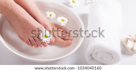 Female feet with spa bowl, towel and flowers on white background #1034040160