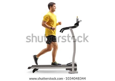 Full length profile shot of a young man running on a treadmill isolated on white background #1034048344