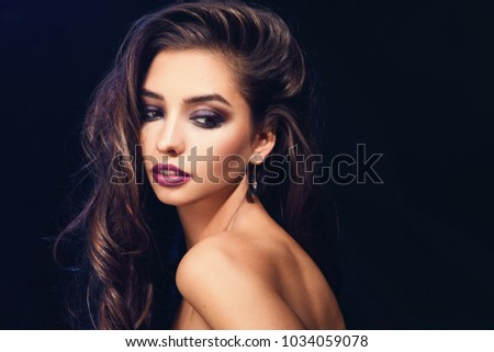 Fashion beauty trend portrait of beautiful brunette girl with long and shiny curly hair. Sexy baby faced model woman with curls hairstyle. Care and beauty of hair. Bright violet lips #1034059078