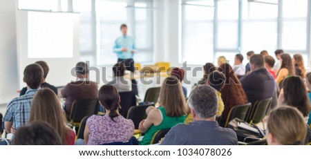 Business and entrepreneurship symposium. Speaker giving a talk at business meeting. Audience in conference hall. Rear view of unrecognized participant in audience. #1034078026