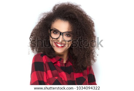 Happy beautiful african american girl with amazing toothy smile posing in checkered shirt. White background. #1034094322