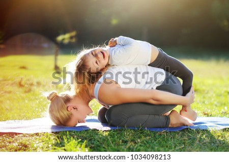 Happy little girl playing with her mom practicing child yoga pose #1034098213