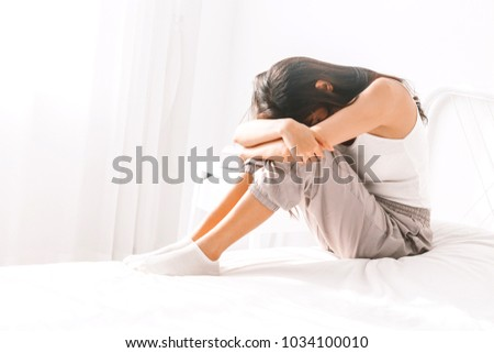 Depressed woman crying on her bed #1034100010