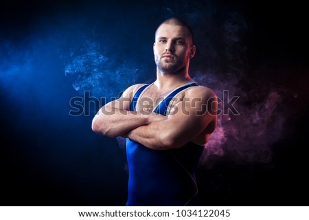 A young sporty man wrestler in a green sports shirt and blue wrestling tights  stands with arms crossed confidently  against a blue and red vape smoke background on a black isolated  #1034122045