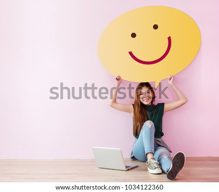 Happy Customer Concept. Review and Feedback her Experience for Satisfaction Survey Online. Young Female in Cheerful Posture, Raise up Speech Bubble with Smiley Face. Sit on the Floor with Laptop Royalty-Free Stock Photo #1034122360