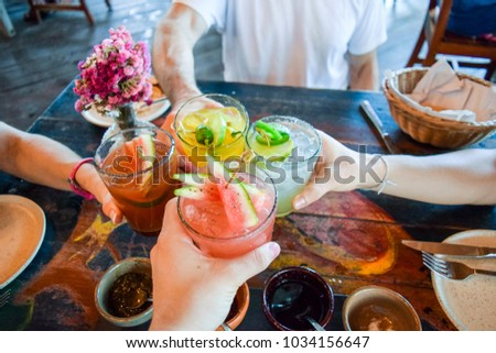 Friends toasting, saying cheers holding tropical blended fruit drinks #1034156647
